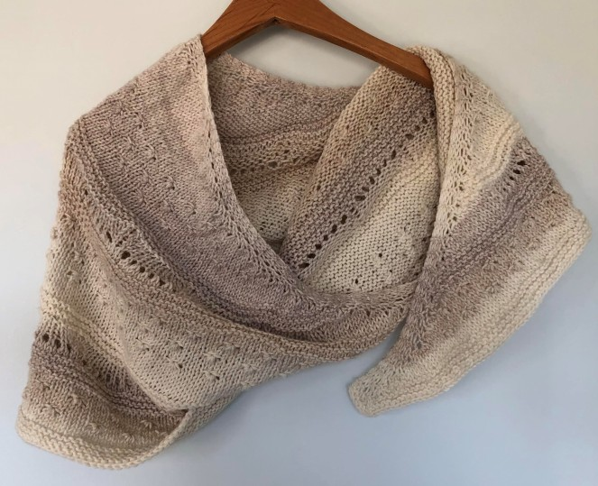 cream and mocha colored shawl draped on wooden hanger