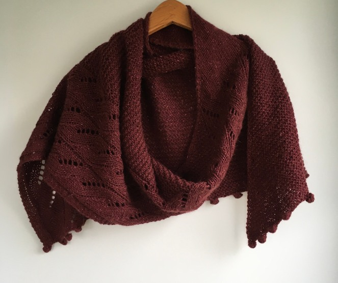 maroon colored shawl with cables and bobbles draped on wooden hanger