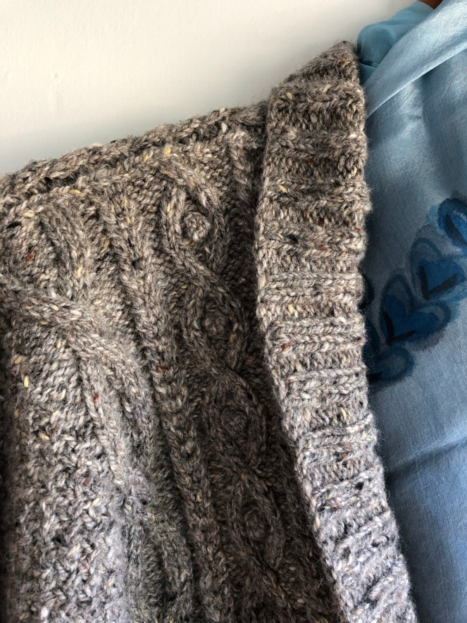 shoulder of gray knit sweater with cables and bobbles
