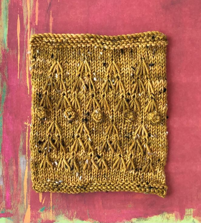 square of gold knitted yarn on maroon background