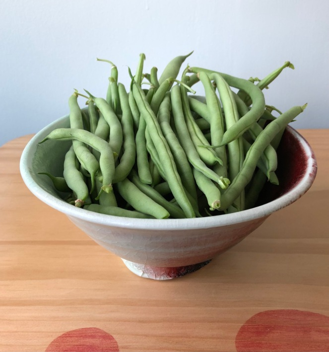 pottery bowl filled with fresh green beans