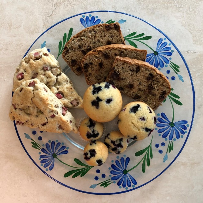 left to right: two triangular scones, three slices of bread, five blueberry muffins on a clear plate with painted blue flowers