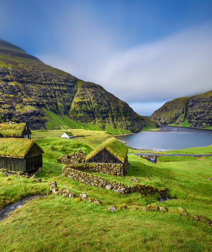 green grass, small stone houses, mountains, blue sky with white clouds