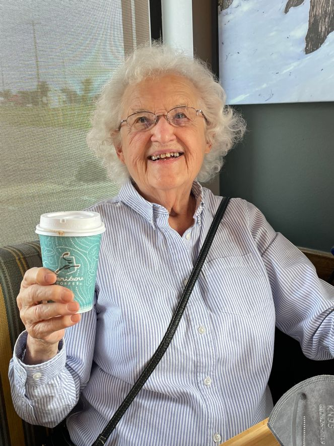 elderly woman with blue striped blouse holding a cup of caribou coffee