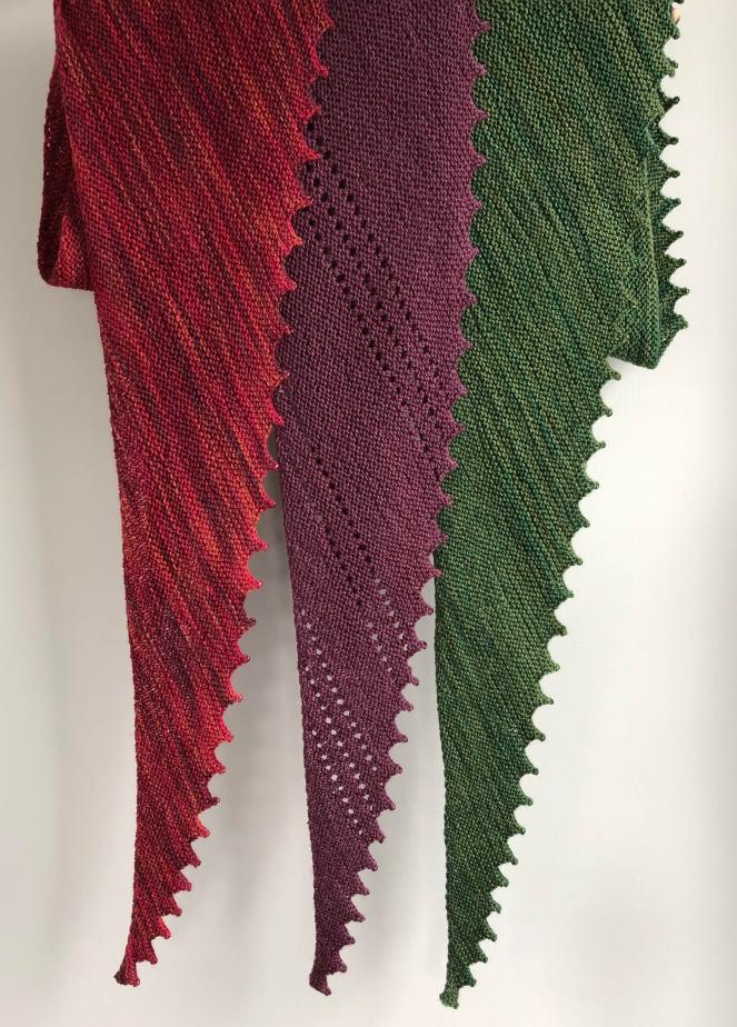 three handknit scarves in red, purple and green